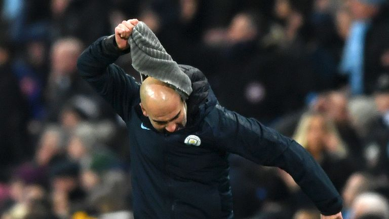 Pep Guardiola pulls off his snood in frustration