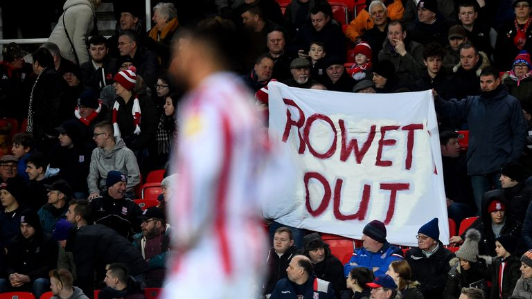 Fans hold a 'Rowett out' sign during  Stoke City's home defeat to Bristol City