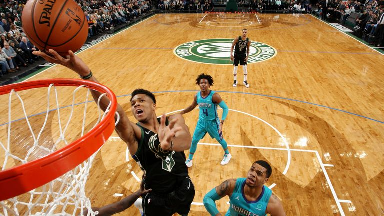 Giannis Antetokounmpo outmuscles the Hornets defense to score an easy basket at the rim