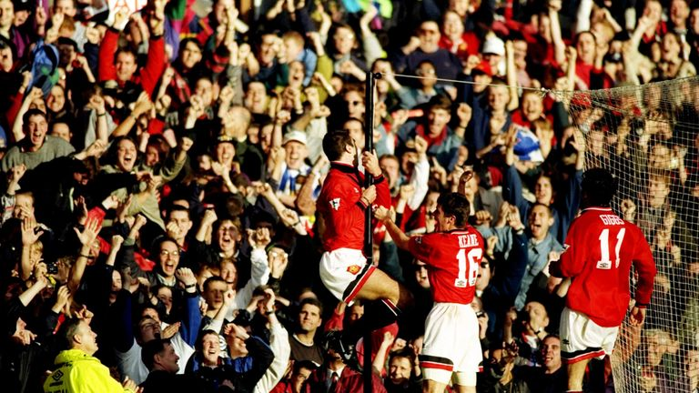 Cantona celebrates his goal with a famous twirl around a pole in front of fans