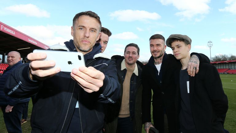 Beckham and son Romeo pose for a photo with England Women's boss Phil Neville and a pair of Salford fans
