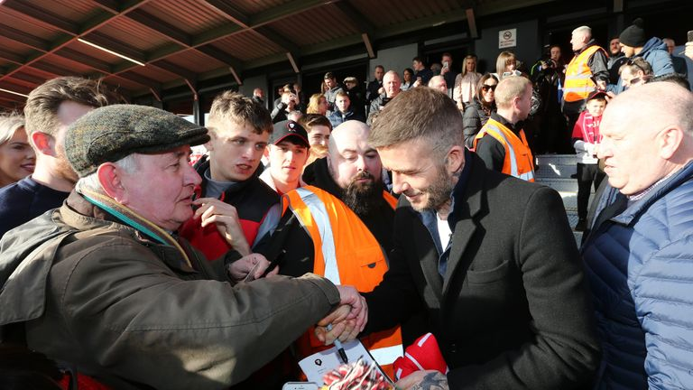 Beckham was happy to sign autographs before the action got under waymobbed by fans at Salford City