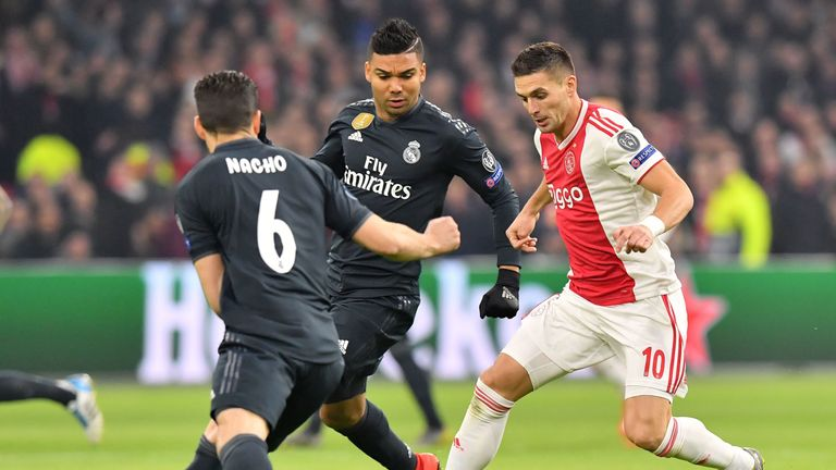 Ajax's Serbian forward Dusan Tadic (R) fights for the ball with Real Madrid's Spanish defender Nacho Fernandez (L) and Real Madrid's Brazilian midfielder Casemiro