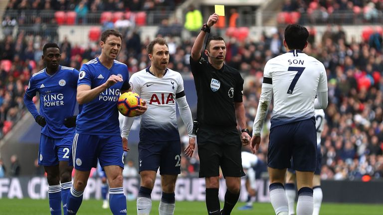Referee Michael Oliver shows a yellow card to Tottenham Hotspur's Heung-Min Son