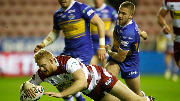 Wigan Warriors' Joe Bullock goes over for a try past Leeds Rhinos' Jack Walker during the Betfred Super League match at the DW Stadium, Wigan. PRESS ASSOCIATION Photo. Picture date: Friday February 8, 2019