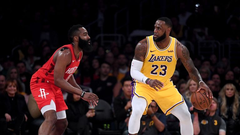 LeBron James of the Los Angeles Lakers backs in on James Harden of the Houston Rockets