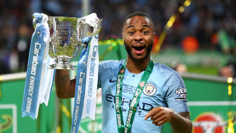 Raheem Sterling celebrates with the Carabao Cup trophy after Manchester City's defeat of Chelsea in February