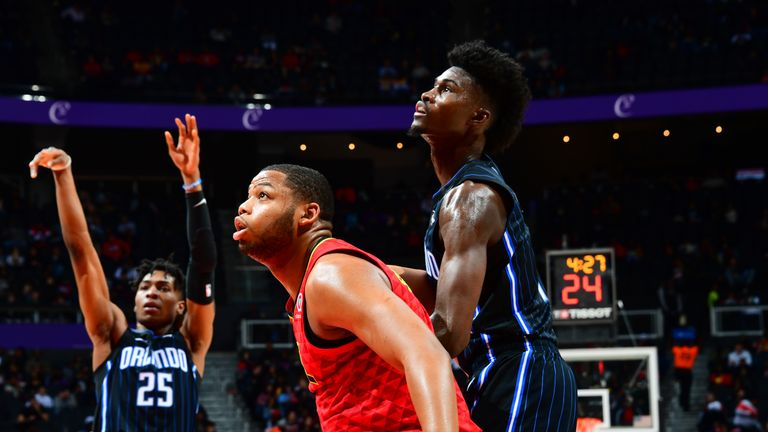 Omari Spellman of the Atlanta Hawks and Jonathan Isaac of the Orlando Magic fight for position for the rebound
