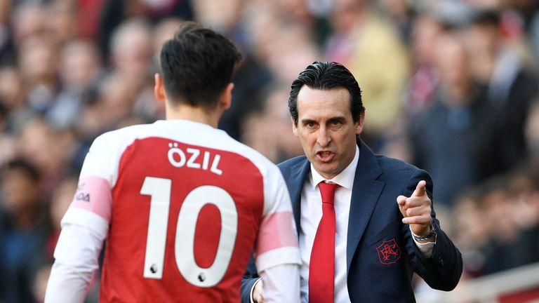Unai Emery speaks to Mesut Ozil during the Premier League match against Southampton at the Emirates Stadium