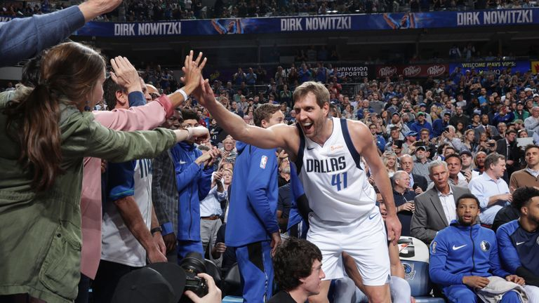 Dirk Nowitzki high-fives Dallas fans after passing Wilt Chamberlain on the NBA all-time scoring list