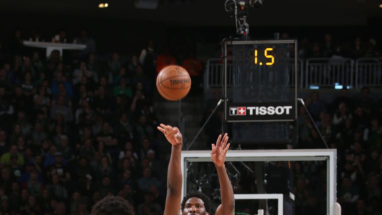 Joel Embiid launches a three-pointer over Giannis Antetokounmpo