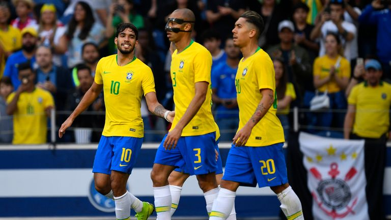 Brazil's players, including Liverpool forward Roberto Firmino (right), celebrate the opening goal in Porto