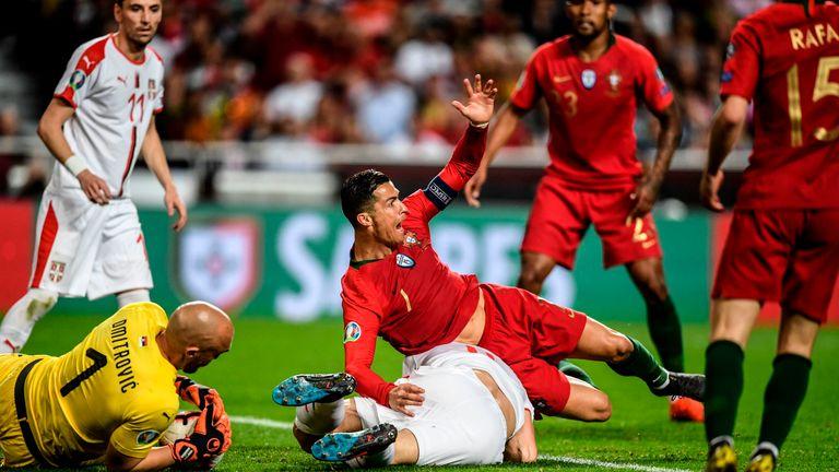 Portugal's Cristiano Ronaldo falls over Serbia's defender Nikola Milenkovic in European Qualifier