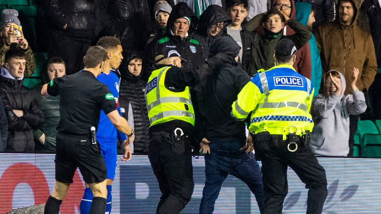A Hibs fan is led away by police after running onto the pitch to confront Rangers captain James Tavernier