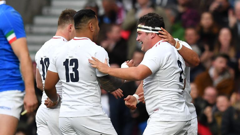 Jamie George celebrates with team-mates after scoring England's first try against Italy
