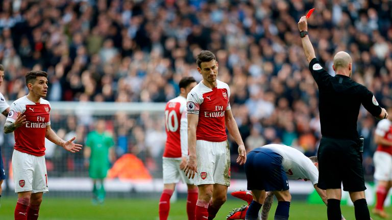 Lucas Torreira (L) is shown a red card by referee Anthony Taylor after a foul on Danny Rose