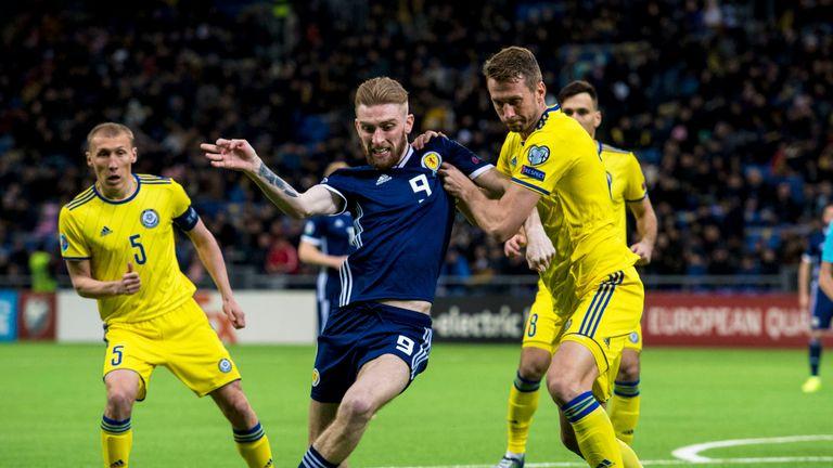 Scotland's Oli McBurnie (L) competes with Kazakhstan's Serhiy Malyi.