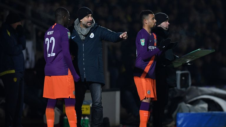 Manchester City's Spanish manager Pep Guardiola (C) talks with Manchester City's French defender Benjamin Mendy (L) as he waits with Manchester City's Brazilian striker Gabriel Jesus to be substituted on during the English League Cup second leg semi-final football match between Burton Albion and Manchester City at the Pirelli Stadium in Burton-upon-Trent, central England on January 23, 2019.