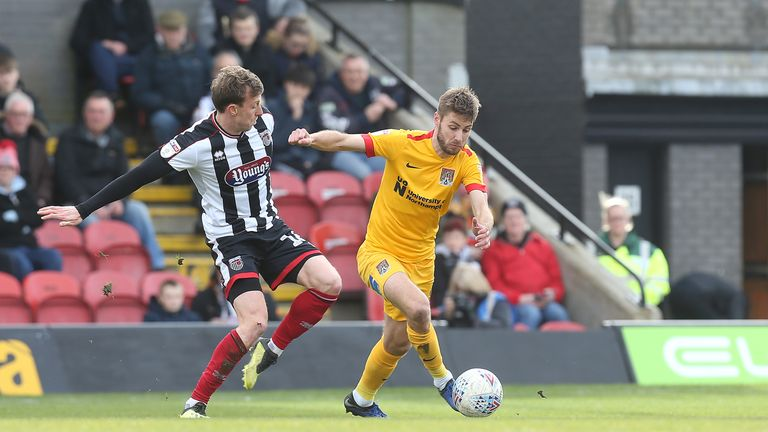 Northampton Town's Sam Foley evades the challenge of Martyn Woolford at Grimsby
