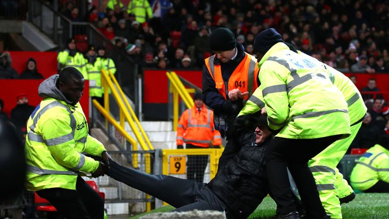 Stewards restraining a fan during a Premier League match between Manchester United and Burnley.