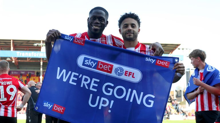 Lincoln City's Bruno Andrade (right) and John Akinde celebrate being promoted after the Sky Bet League Two match at Sincil Bank