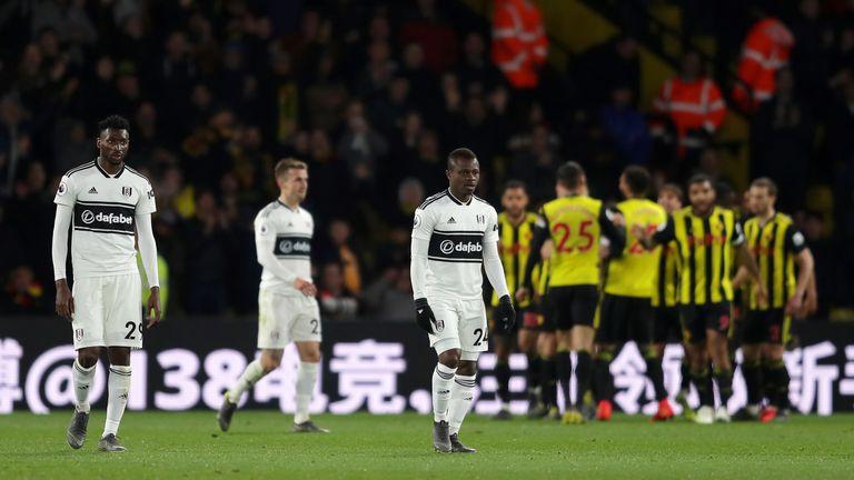 Fulham's Andre Zambo Anguissa and Jean Michael Seri look dejected as Watford celebrate scoring