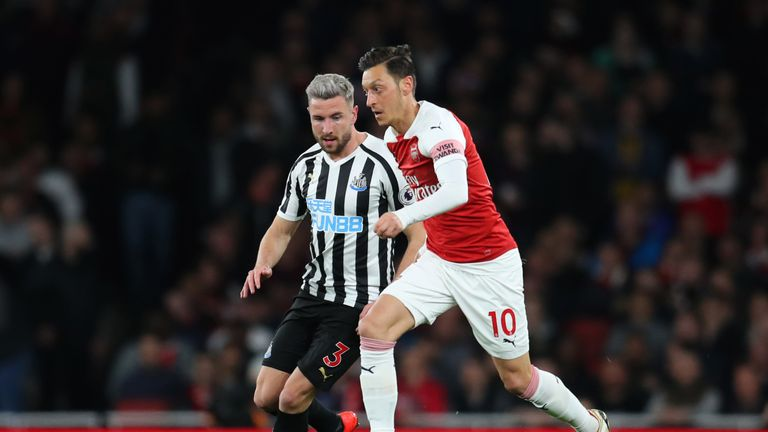 Mesut Ozil tussles for the ball