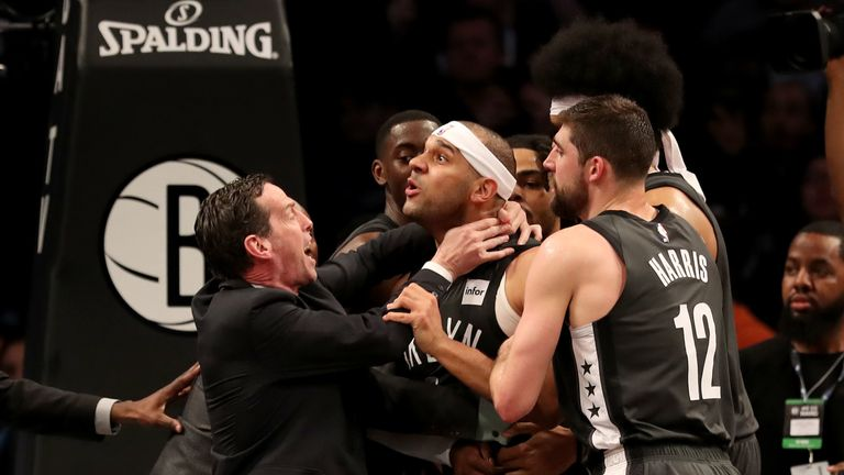 Head coach Kenny Atkinson and Joe Harris of the Brooklyn Nets hold back Jared Dudley at Barclays Center after a foul by Joel Embiid of the Philadelphia 76ers in the third quarter