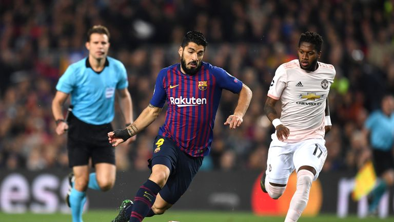 Barcelona's Luis Suarez runs with the ball away from Fred