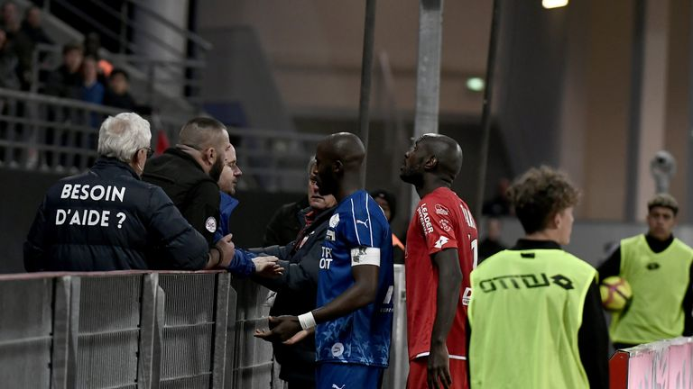 Gouano confronts a fan on the touchline after hearing alleged racist chants