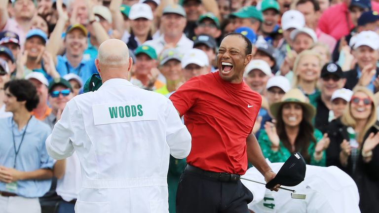 Tiger Woods celebrates with caddie Joe LaCava after putting to win The Masters 2019