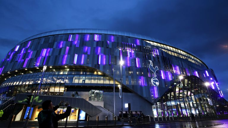 A passer-by takes a photo outside an illuminated Tottenham Hotspur Stadium