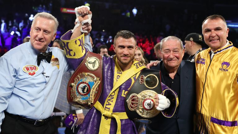 Vasyl Lomachenko celebrates with his WBO and WBA titles