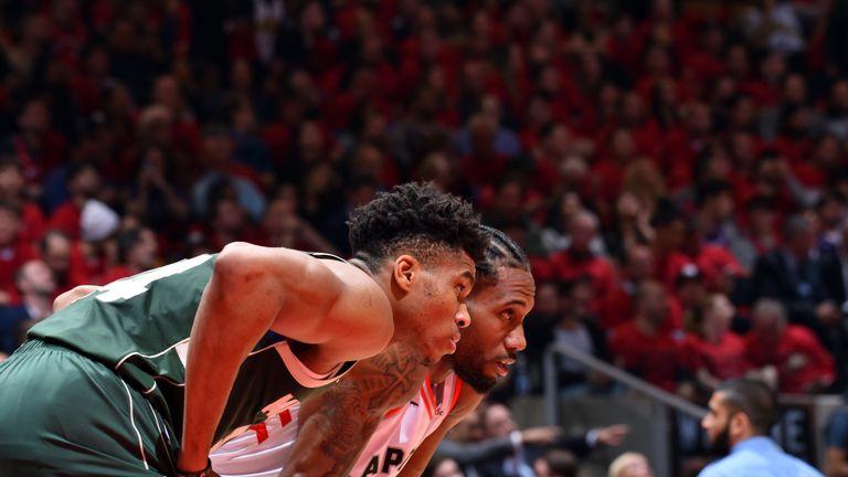 Giannis Antetokounmpo and Kawhi Leonard prepare to contest a rebound