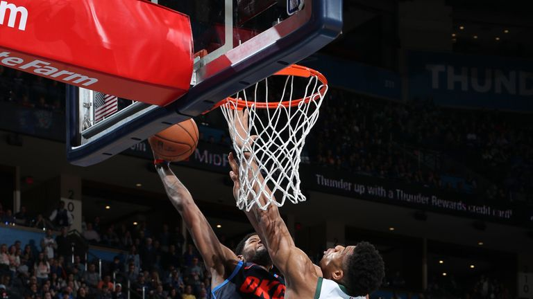 Giannis Antetokounmpo attempts to block a Paul George dunk