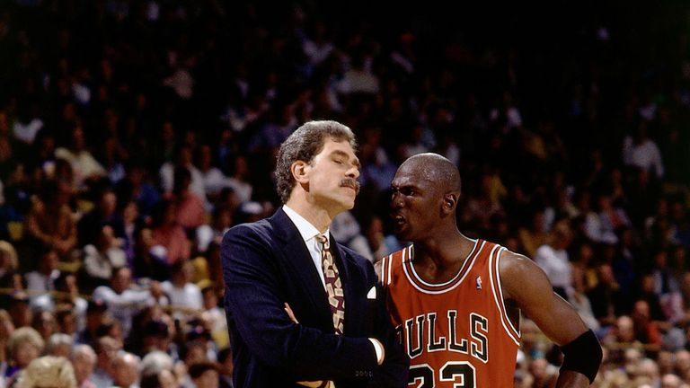 Phil Jackson talks with Michael Jordan during a Chicago Bulls game