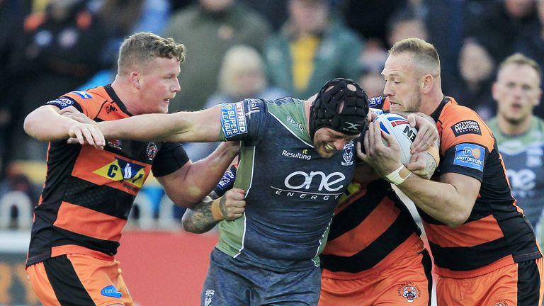 Adam Milner, Nathan Massey and Liam Watts tackle Warrington's Chris Hill