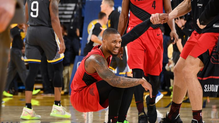 Damian Lillard #0 of the Portland Trail Blazers is helped up by his teammate during Game Two of the Western Conference Finals against the Golden State Warriors on May 16, 2019 at ORACLE Arena in Oakland, California.