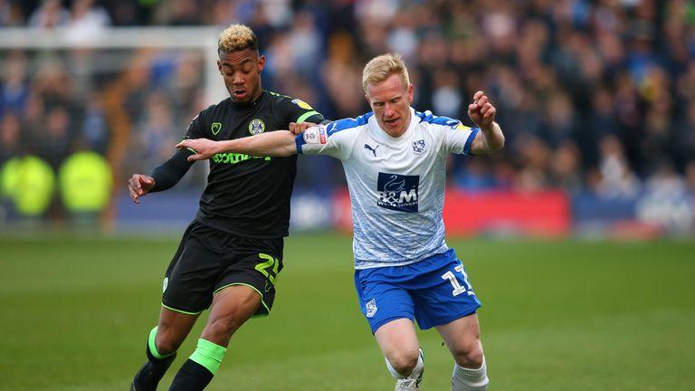 Tranmere's David Perkins and Forest Green striker Junior Mondal battle for possession