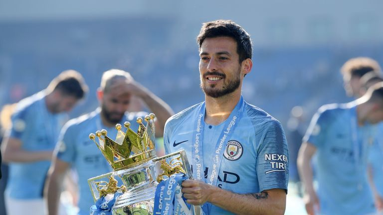 David Silva poses with the Premier League trophy after Manchester City retain the title