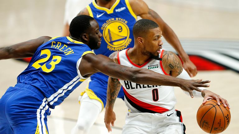 Damian Lillard #0 of the Portland Trail Blazers battles for the ball with Draymond Green #23 of the Golden State Warriors during the first half in game three of the NBA Western Conference Finals at Moda Center on May 18, 2019 in Portland, Oregon.