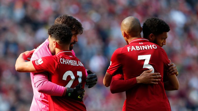 Liverpool players Alex Oxlade-Chamberlain, Alisson Becker, Fabinho and Joe Gomez embrace at full-time after Liverpool miss out in the Premier League title