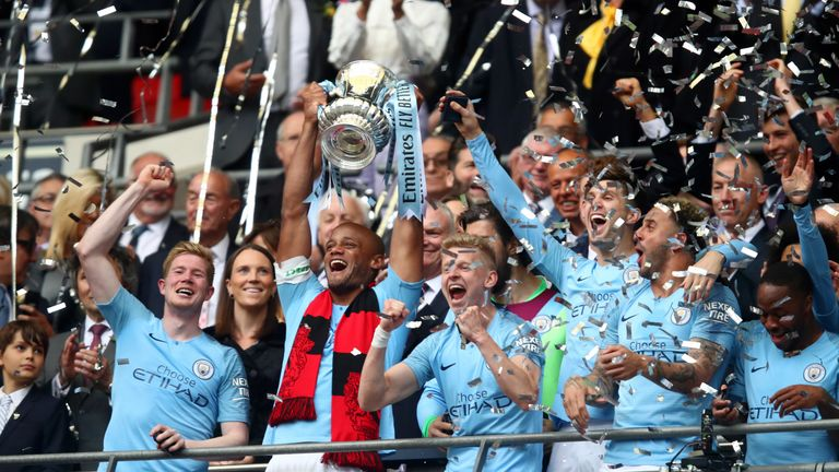 Manchester City captain Vincent Kompany lifts the FA Cup after playing his final game for the club