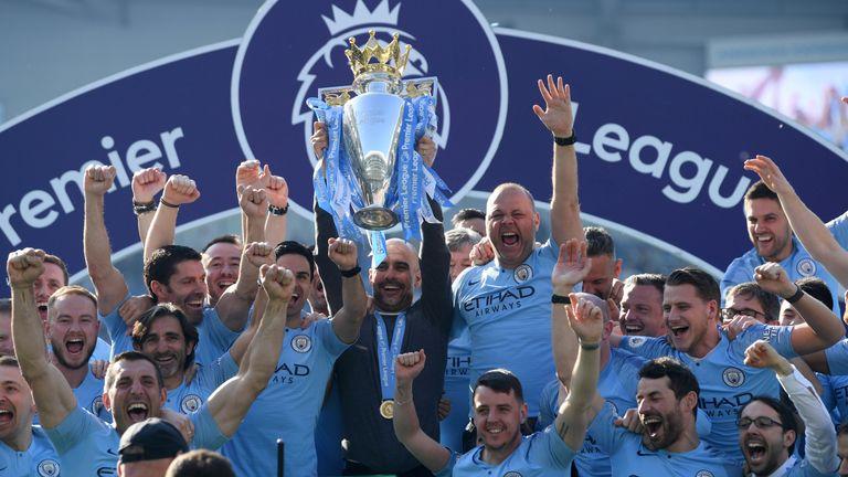 Pep Guardiola lifts the Premier League trophy after Manchester City retain the title