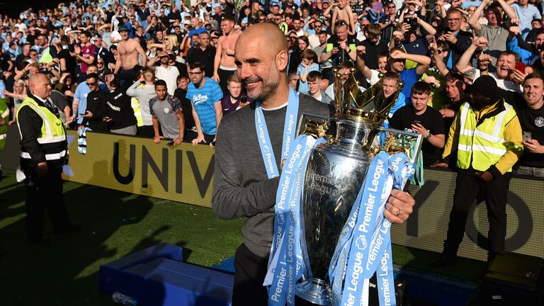 Pep Guardiola celebrates with the Premier League trophy in front of Manchester City fans at the AMEX Stadium