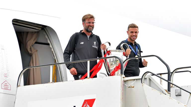 Jurgen Klopp and Jordan Henderson emerge from the plane with the Champions League trophy