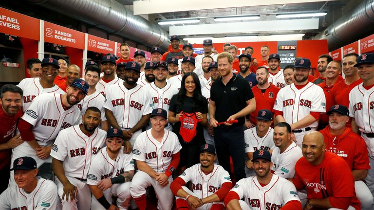 Prince Harry and Meghan, Duchess of Sussex pose for a picture with players of the Boston Red Sox.