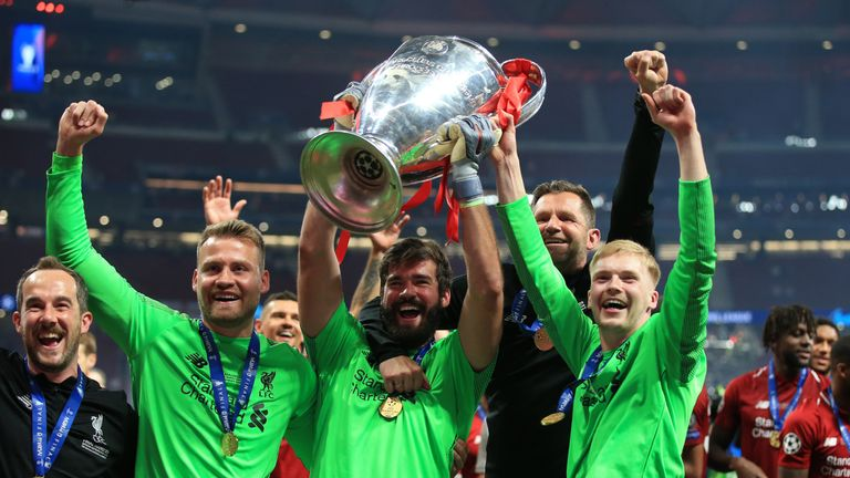 Liverpool goalkeepers Simon Mignolet, Alisson Becker and Caoimhin Kelleher celebrate with the Champions League trophy