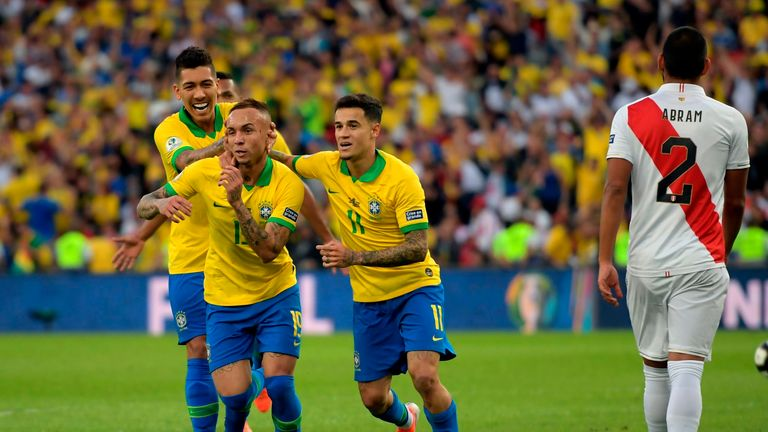 Everton (C) celebrates with Brazil team-mates Roberto Firmino (L) and Philippe Coutinho after scoring against Peru