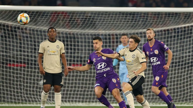 Perth Glory's Joel Chianese and Man Utd's Daniel James contest for the ball